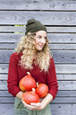 Young woman by wooden shed holding squash, looking away - CUF13786