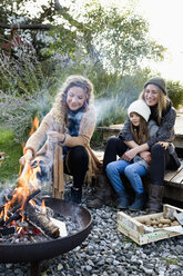 Two women and girl sitting by fire pit, relaxing - CUF13804