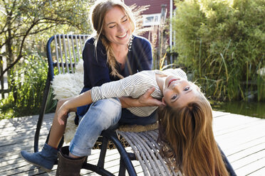 Girl sitting on mother's lap, leaning back - CUF13810