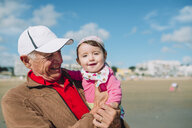 France, La Baule, portrait of baby girl on grandfather's arms on the beach - GEMF02018
