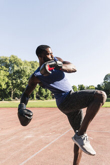Young Afro-American man training boxing on sports field, outdoors - UUF13870