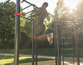 Muscular young man exercising on parcours bars - UUF13879