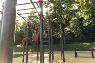 Muscular young man exercising on parcours bars - UUF13882
