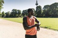 Young athlete in training on sports field taking the time on his smartwatch - UUF13891
