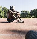 Young athlete sitting on sports field, listening music - UUF13912
