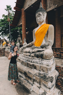 Thailand, Ayutthaya, mother and little daughter standing besides Buddha statue at Wat Yai Chaya Mongkhon - GEMF02026