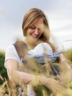Portrait of happy mother carrying her little daughter in baby sling in nature - LAF02041