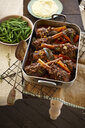 Overhead view of lamb shank stew in roasting tin with green beans and mashed potato - CUF13852