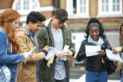 Young adult college students reading exam results on campus - CUF13993