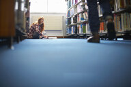 Young female college student looking up whilst working on library floor - CUF13996