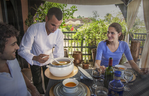 Waiter serving young couple soup, Marrakesh, Morocco - CUF14152