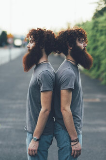 Portrait of identical adult male twins with red hair and beards back to back on sidewalk - CUF14215