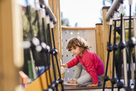 Portrait of little girl on climbing frame at playground - JSMF00208