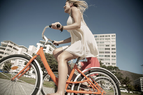 Young woman cycling past buildings, Cape Town, South Africa - CUF14302