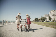 Young women walking with bicycle on seafront, Cape Town, South Africa - CUF14305