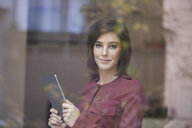 Portrait of businesswoman holding digital tablet looking through window - CUF14317