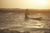 Silhouette of young male surfer and surfboard in sea, Devon, England, UK - CUF14335