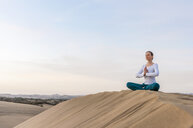 Woman practicing yoga lotus pose on top of dune, Maspalomas, Gran Canaria, Canary Islands, Spain - CUF14371