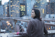 Female tourist looking out from Brooklyn Bridge, New York, USA - CUF14419