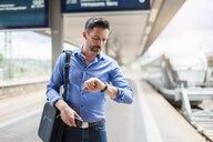 Mature businessman checking wrist watch on railway platform - CUF14464