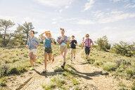 Teenage girl and adult friends running on dirt track, Bridger, Montana, USA - CUF14518