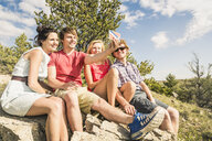 Young man and friends taking smartphone selfie sitting on rocks, Bridger, Montana, USA - CUF14527