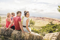 Portrait of teenage girl and adult friends looking over their shoulder on rocks, Bridger, Montana, USA - CUF14551
