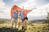 Portrait of young man and female friends holding up blanket on windy hill, Bridger, Montana, USA - CUF14560
