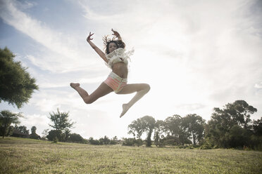 Young woman jumping in mid air, arms raised looking at camera smiling - CUF14587