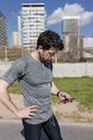 Sportive man with cell phone and earphones in urban area - MAUF01394