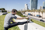 Sportive man stretching in urban area - MAUF01400