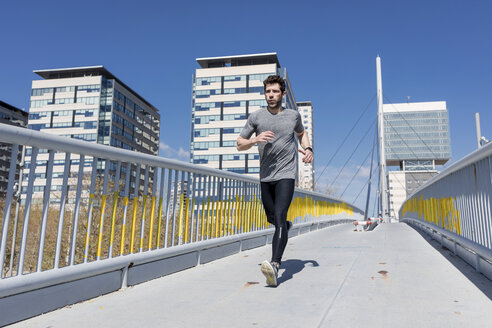 Sportive man runinng on a bridge in the city - MAUF01403