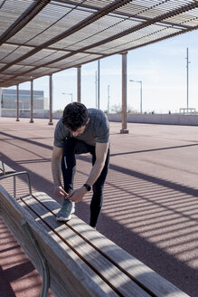 Sportive man lacing his shoes on a bench under roofing - MAUF01406