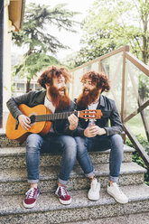 Young male hipster twins with red beards sitting on stairway playing guitar - CUF14649
