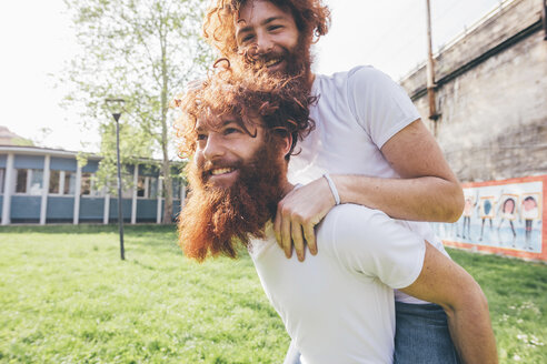 Young male hipster twins with red beards piggy backing in park - CUF14652