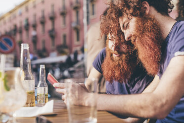 Young male hipster twins with red hair and beards reading smartphone texts at sidewalk bar - CUF14655