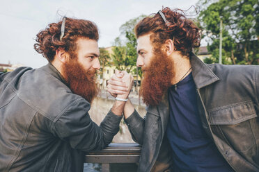 Young male hipster twins with red hair and beards arm wrestling on bridge - CUF14658