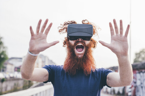 Portrait of young male hipster with red hair and beard screaming whilst wearing virtual reality headset - CUF14667