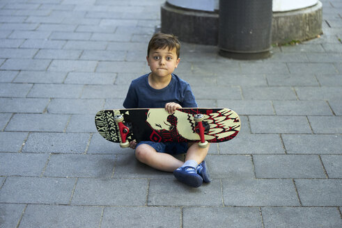 Portrait of astonished little boy sitting on pavement with skateboard - BEF00105