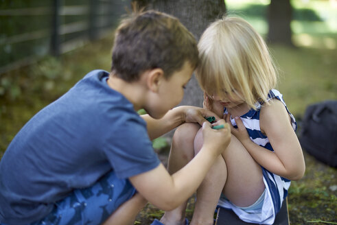 Boy painting on knee of his little sister - BEF00108