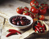 Black olives, red chilli peppers and vine tomatoes in rustic bowl and wooden ladle - CUF14715