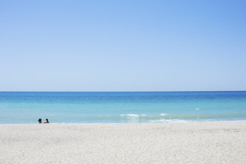 Distant view of two women relaxing on beach at Cilento coast, Italy - CUF14784