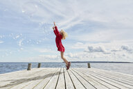 Young girl on wooden pier, jumping to reach bubbles - CUF14829