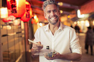 Man holding sushi with chopstick looking at camera laughing - CUF14937