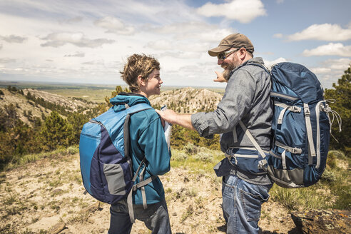 Hiking father and teenage son pointing over landscape, Cody, Wyoming, USA - CUF15048