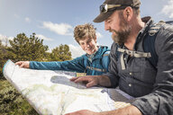 Hiking father and teenage son sitting reading folding map, Cody, Wyoming, USA - CUF15051