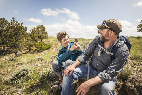 Teenage boy photographing father on hiking trip, Cody, Wyoming, USA - CUF15054