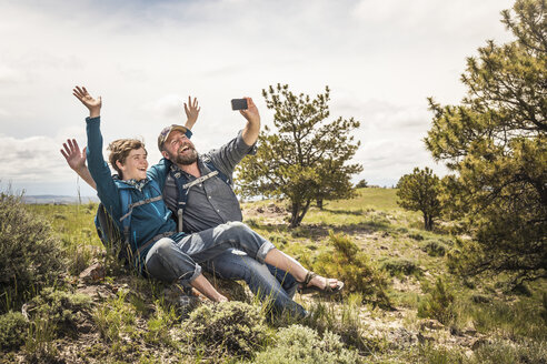 Father and teenage son waving for selfie on hiking trip, Cody, Wyoming, USA - CUF15057