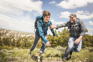 Father and teenage son chasing each other on hiking trip, Cody, Wyoming, USA - CUF15063