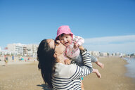 France, La Baule, mother kissing happy baby girl on the beach - GEMF02029